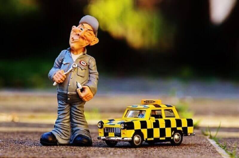 車と整備士がモンキーレンチを持った画像