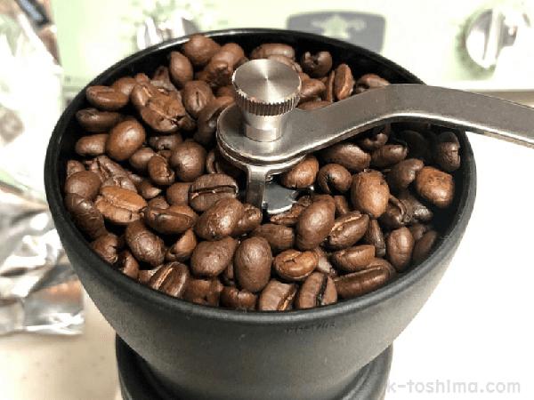 手挽きコーヒーミルのホッパーとコーヒー豆の画像