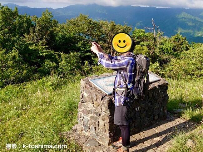 山頂で写真を撮る男性